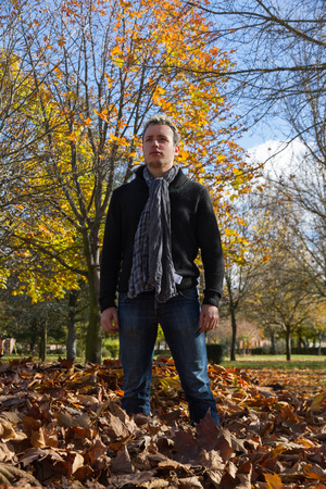beardless: Young man with scarf around his neck standing on fallen leaves in autumn park  Stock Photo