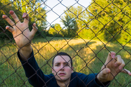 beardless: Young man in nature and behind a fence or wire mesh at sunset