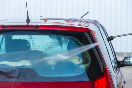 soaping: Wash car rear window by hand with water jet pressure  Stock Photo