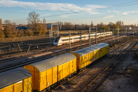 Moving train and train cars freshly painted yellow on the tracks with sunset light