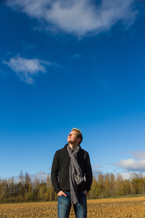 beardless: Young man with his face to the sun and eyes closed in a plowed field with trees and blue sky with clouds