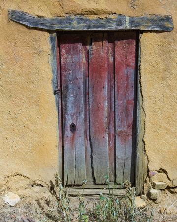 lintel: Wooden door painted red, old, unpainted and in rural construction