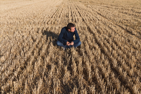 insolación: Joven mujer sentada en el suelo de un campo de cereales segado en la observación y la actitud reflexiva con respecto a su izquierda