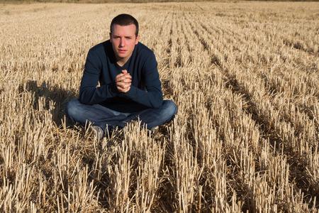 insolación: Joven sentado en el suelo en el campo de cereales segado con los dedos las manos entrelazadas y mirando a la cámara