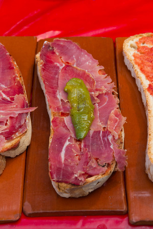 anointed: Slices of bread smeared with tomato and sliced ham   pan tumaca   with green pepper