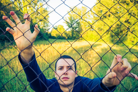 Young man looking at camera after prisoners wire or wire mesh in nature