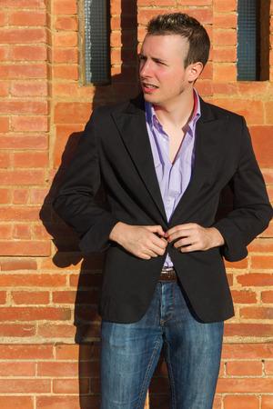 beardless: Young man buttoning his jacket in the sun in front of a brick wall - Hombre joven abotonandose la chaqueta al sol, delante de una pared de ladrillo