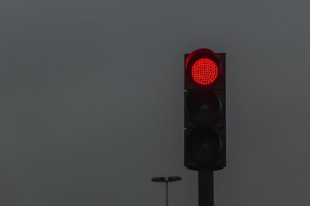 Red traffic light on dark sky photo
