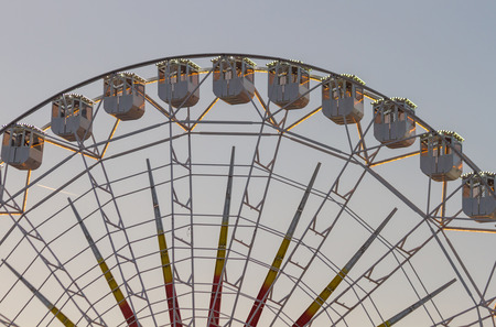 Great Ferris Wheel Fair with booths, illuminated at dusk and plane with trace in the sky  photo