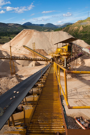 size distribution: Machinery and classification according gravel size distribution via conveyor belts and piles of sand and records in mountain landscape