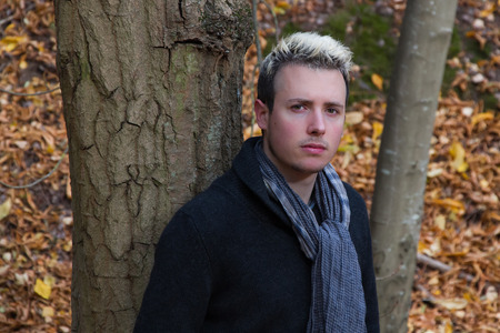 beardless: Young Man in autumnal park between trees with fallen leaves and looking at camera Stock Photo