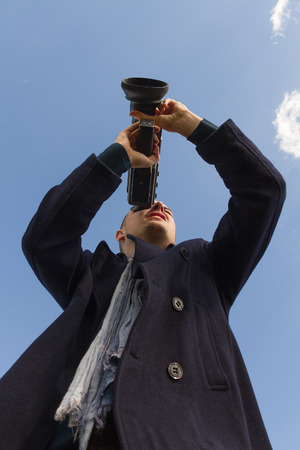 super 8: Young man with a camera filming Super 8 mm film seen from below and sky background