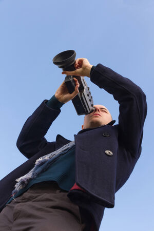 Young man with a camera filming Super 8 mm film seen from below and sky background photo