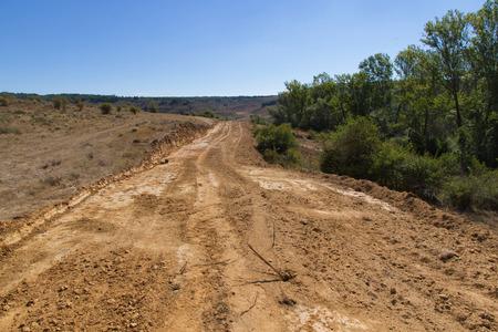 Compensación para explanar, nivelar y desbroce de la vegetación en el campo de la tierra para la construcción de la carretera o autopista Foto de archivo