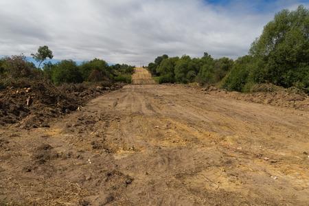 Compensación de explanar, nivelar y desbroce de la vegetación en el campo de la tierra para la construcción de la carretera o autopista