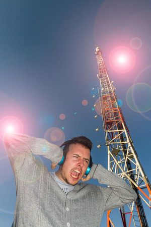 beardless: Young Man with Headphones sound or music, with expression of receiving a brutal volume, surrounded by effect of light and antenna or Telecommunications tower Stock Photo