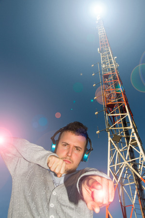 i beam: Young Man DJs with helmets or headphones sound or music, surrounded by effect of light and antenna or Telecommunication tower