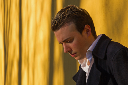 medium body: Young man looking down, with jacket, in front of an illuminated with warm rays of sunset wall