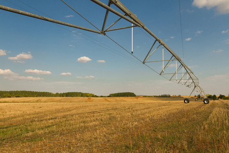 harvested: Structure irrigation system self-propelled mobile Spray (pivot) in harvested grain field