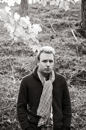 beardless: Young man looking at camera in autumnal setting with neck scarf
