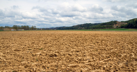 recently: Recently Landscape with plowed land, houses and hills with trees in the background Stock Photo