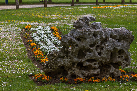 volcanic rock: Rectangular flower bed in white and orange, Planted in the earth at a backyard park, volcanic rock with a header. Surrounded by grass Also full of wild flowers, a path with trees in the background