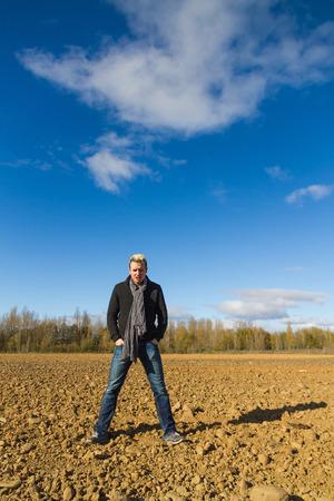 manos: Young sun in a plowed land with trees and blue sky with clouds and angry gesture Man lo, manos en los bolsos, dia,  cielo, azul, plano medio, ira, gesto, cara