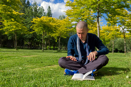 comprising: Young man with cropped hair sitting on the grass in a park, cross-legged and implementing or following instructions from a book to read the lines of the hand