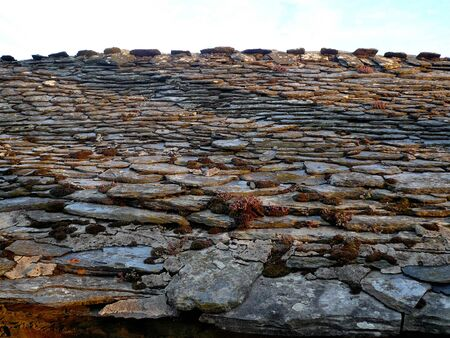 slate roof: Detail of old slate roof with moss and lichen, In rural area at sunset Stock Photo