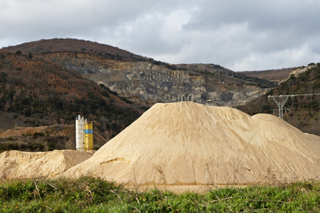 gravel pit: Pierced mountain quarry for stone quarrying and sand. Sand Mountain gravel pit in the foreground in silos and electrical turret