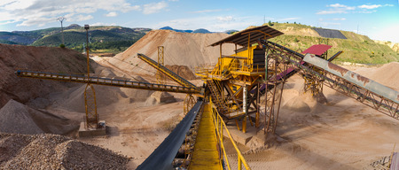 Panoramic gravel pit in mountain area with machinery and distribution tapes gravel according sizes lots of gravel and sand for construction industry