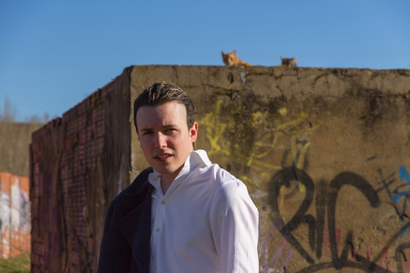 medium body: Smart young man outdoors white shirt and jacket hanging man bottom painted brick wall with graffiti and cats at the top