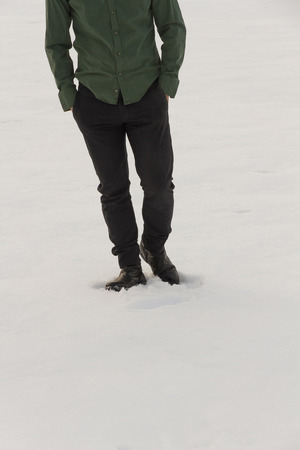 medium body: Front view of lower body halfdressed man walking in the snow with his hands in his pockets