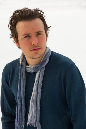 beardless: Portrait of young man looking at camera with sweater and blue scarf around his neck