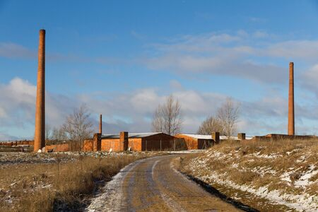 xx century: Former factory tiles and bricks with traces of winter snow. With three tall chimneys and dirt road in foreground Stock Photo