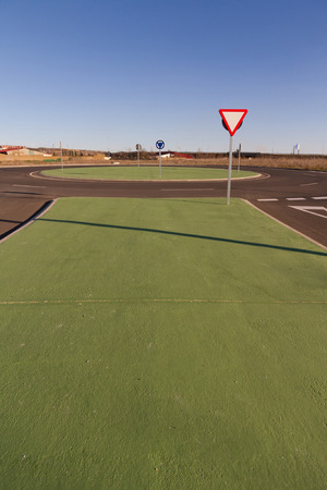 roundabout: Roundabout roundabout or new construction. Designed to simulate grass green painted cement. Outside urban space. With vertical traffic signs and corresponding asphalt