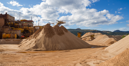 classifier: Panoramic view of gravel stone crushing mills with ribbons and gravel distribution according to sizes in gravel pit outdoor and piles of gravel and sand Stock Photo