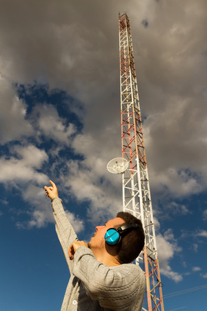 vj: Young man with headphones or earphones sound or music next to a Telecommunications Tower pointing up at the sunset sky with clouds Stock Photo