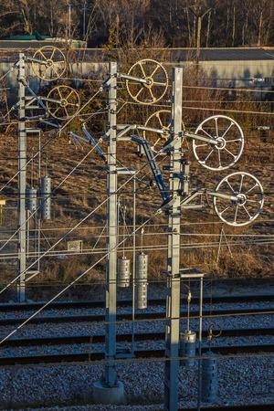 pulleys: Los sistemas de compensaci�n de tensi�n mec�nica en las estructuras contrapesos cable poleas y engranajes de metal de catenaria o de l�nea a�rea en tren Foto de archivo