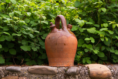 pileup: Clay ceramic jug perched on a stone wall and surrounded by vegetation