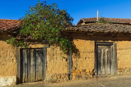 puertas antiguas: Los viejos edificios rurales, en ruinas, hechas con adobe y puertas de madera. En la fachada brota una planta con frutos de saúco negro
