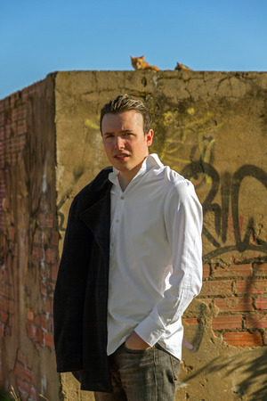 medium body: Smart young man, outdoors, white shirt and jacket hanging man, bottom painted brick wall with graffiti and cats at the top