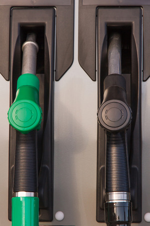 energy suppliers: Two jet nozzles or hoses with tap for dispensing fuel at a gas station