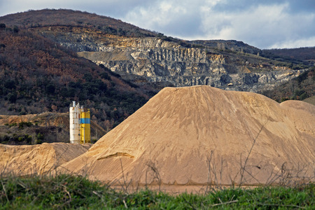 gravel pit: Pierced mountain quarry for stone quarrying and sand. Sand Mountain gravel pit in the foreground in silos Stock Photo