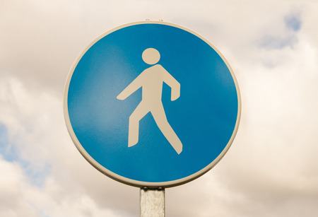 mandatory: Traffic signal circular blue isolated on white background of cloudy sky. Mandatory route for pedestrians