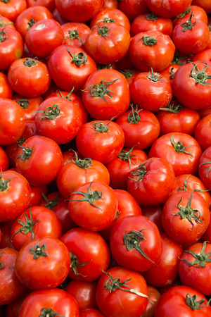 unwashed: Freshly pulled from the ground and unwashed, on display for sale at outdoor market natural tomatoes