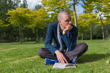 dispersed: Young man with cropped hair sitting on the grass in a park and cross legged with a book in hand, looking around dispersed Stock Photo