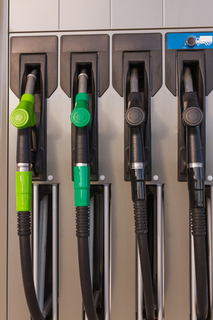 energy suppliers: Four jet nozzles or hoses with tap for dispensing fuel at a gas station Stock Photo