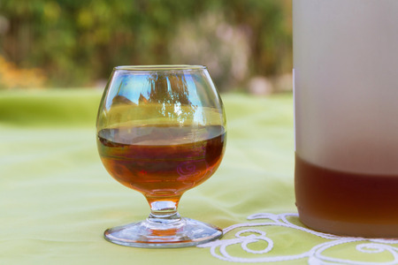 spirituous beverages: Glass cup with roasted alcoholic liquor brandy cafe beside translucent, on a table with embroidered tablecloth, outdoors bottle. The cup presents reflections rustic environment house, sky and trees