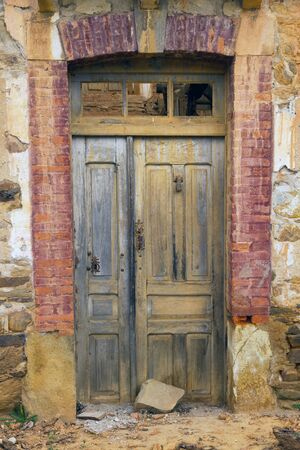 caller: Old wooden door, muddy, with the caller, and rusty locks, in a country house in ruins Stock Photo